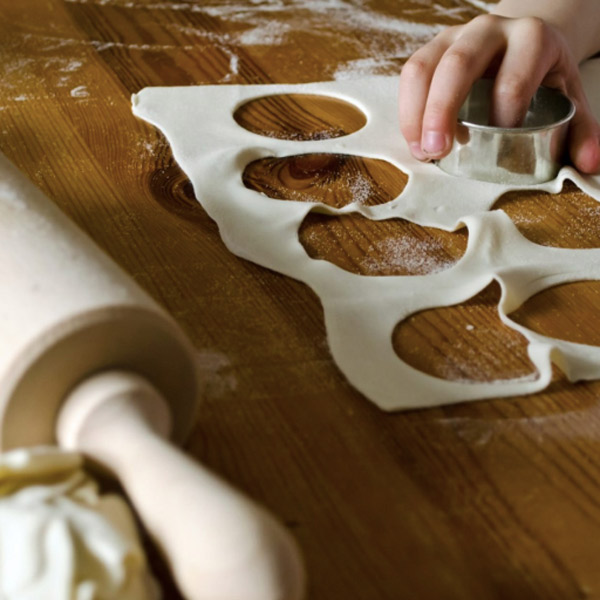 Student using a biscuit cutter to make circles from dough