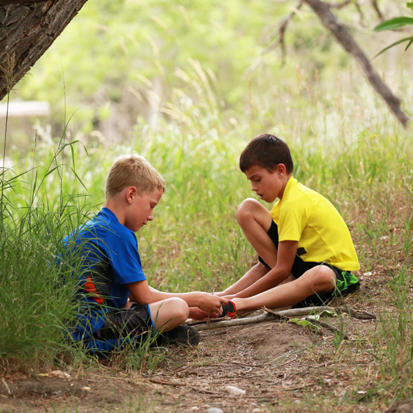 Two boys with sticks at CSU's Environmental Learning Center (ELC)