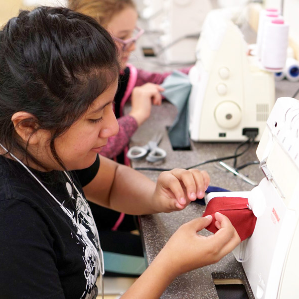 Students using sewing machines at summer Fashion FUNdamentals