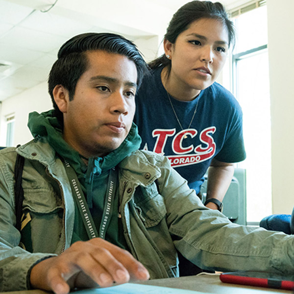 Native American student and instructor viewing a laptop screen