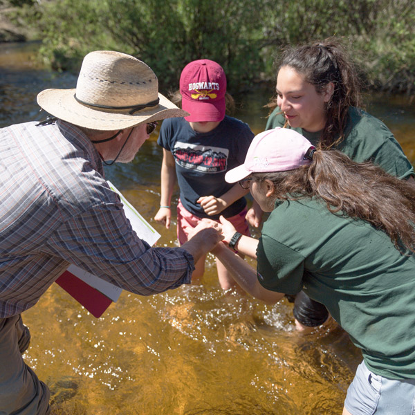 Instructor and students collaborating in a mountain stream